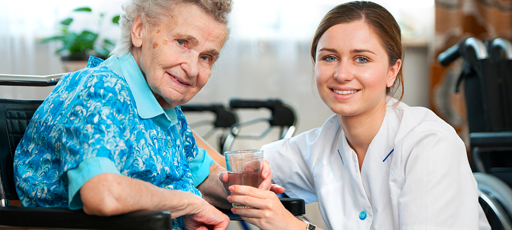 caregiver giving water to patient
